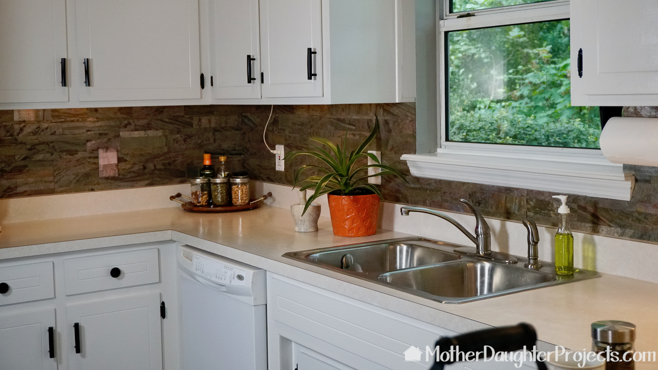 Learn how to do a mini kitchen makeover by painting kitchen cabinets with latex paint, installing a pull out trash can, and installing DIY light fixtures.