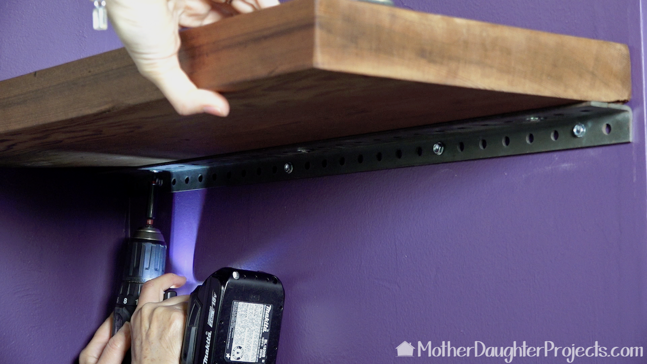 Using a Makita drill to attach the angle iron to the wall and then to the board.