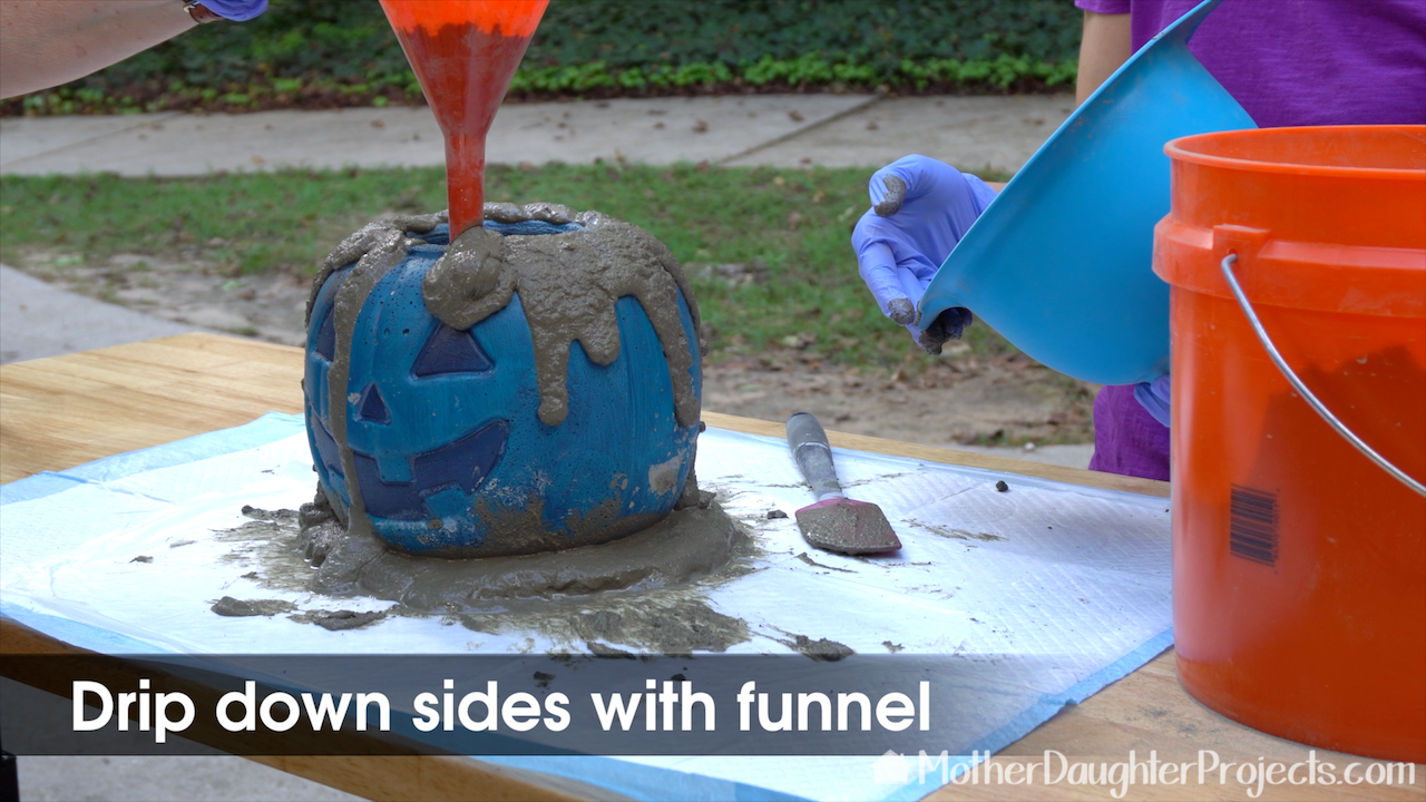 Use a funnel to drip the concrete all around the pumpkin.