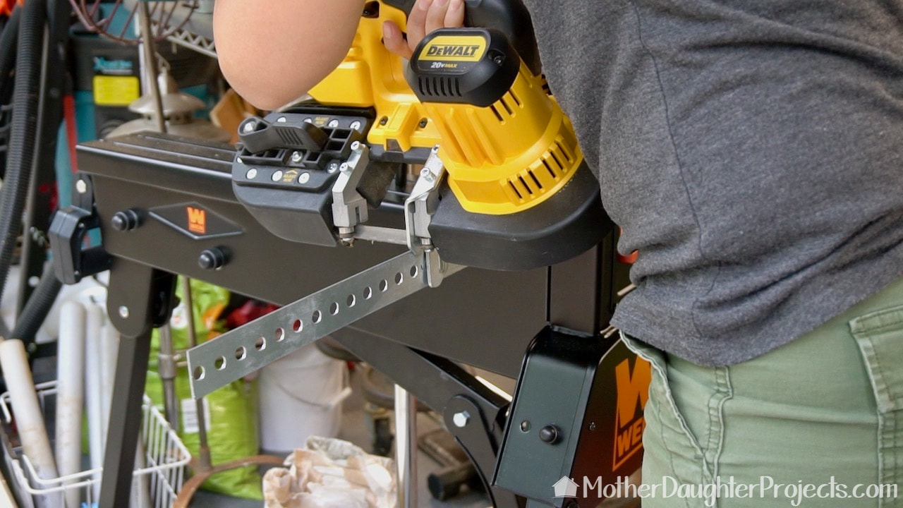 Cutting the slotted metal flat bar with a DeWalt battery powered band saw.
