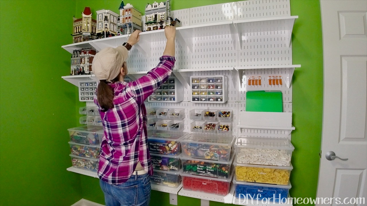 Lego houses are displayed on the upper shelves of the Lego display and storage wall.