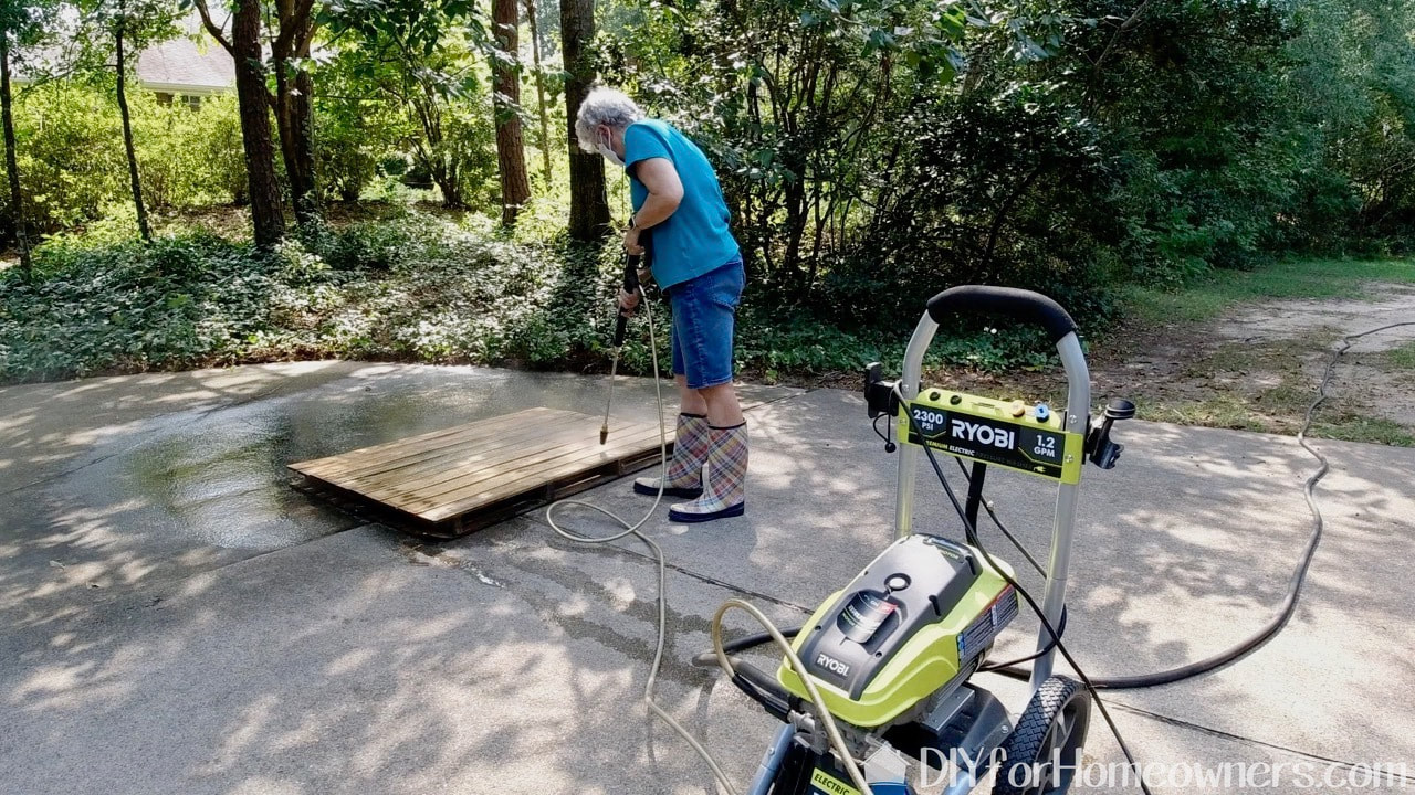Pressure washing the dirty pallets with a Ryobi pressure washer.