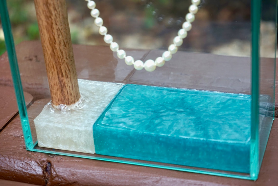 Vintage pearl necklace in glass display case with epoxy base.