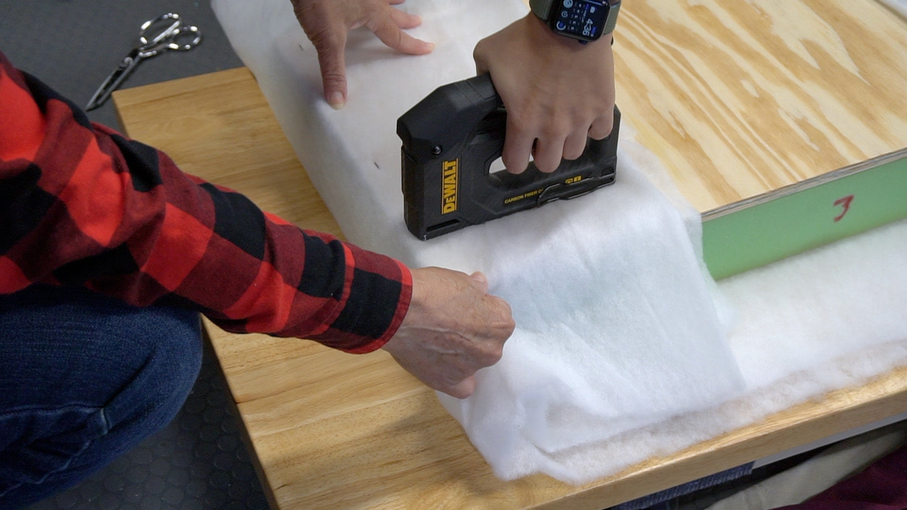 Using a DeWalt Carbon Fiber tacker to secure the batting to the plywood on the footstool.
