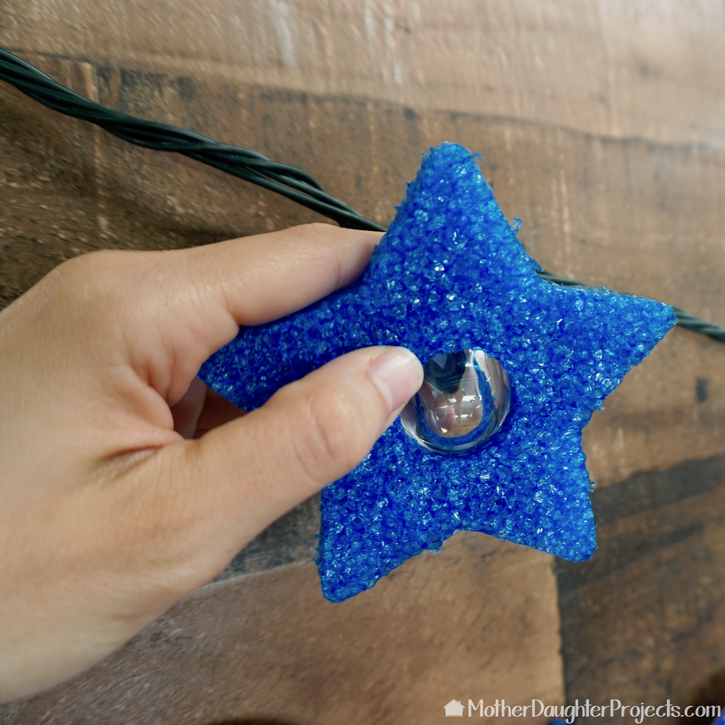Add the stars to the strand light bulbs.