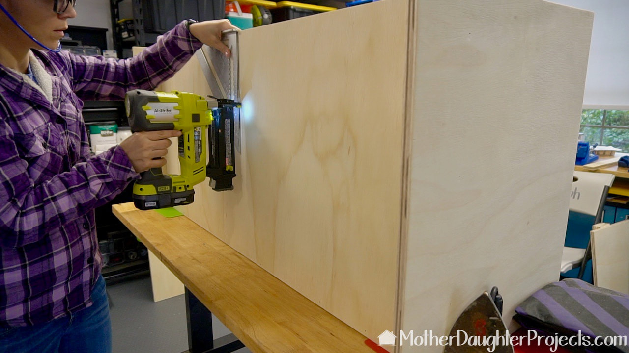 Using a Ryobi brad nailer to secure the body of the TV stand.