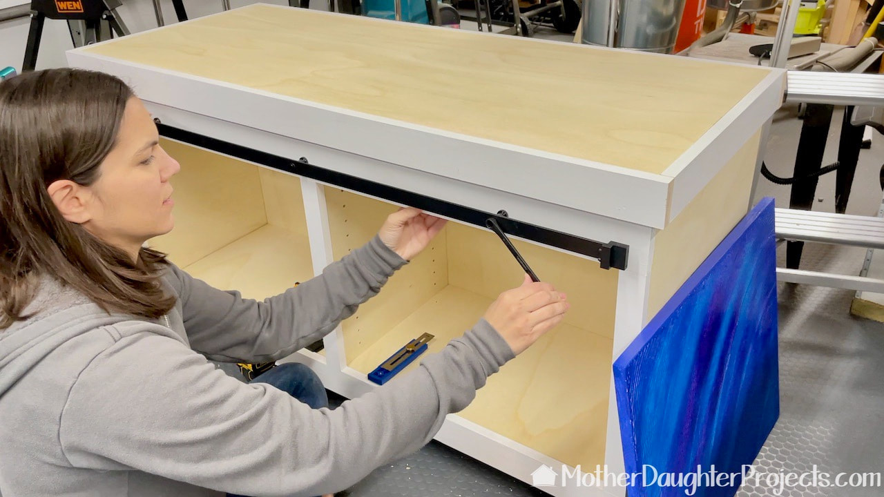 Attaching the sliding door hardware to the face frame.