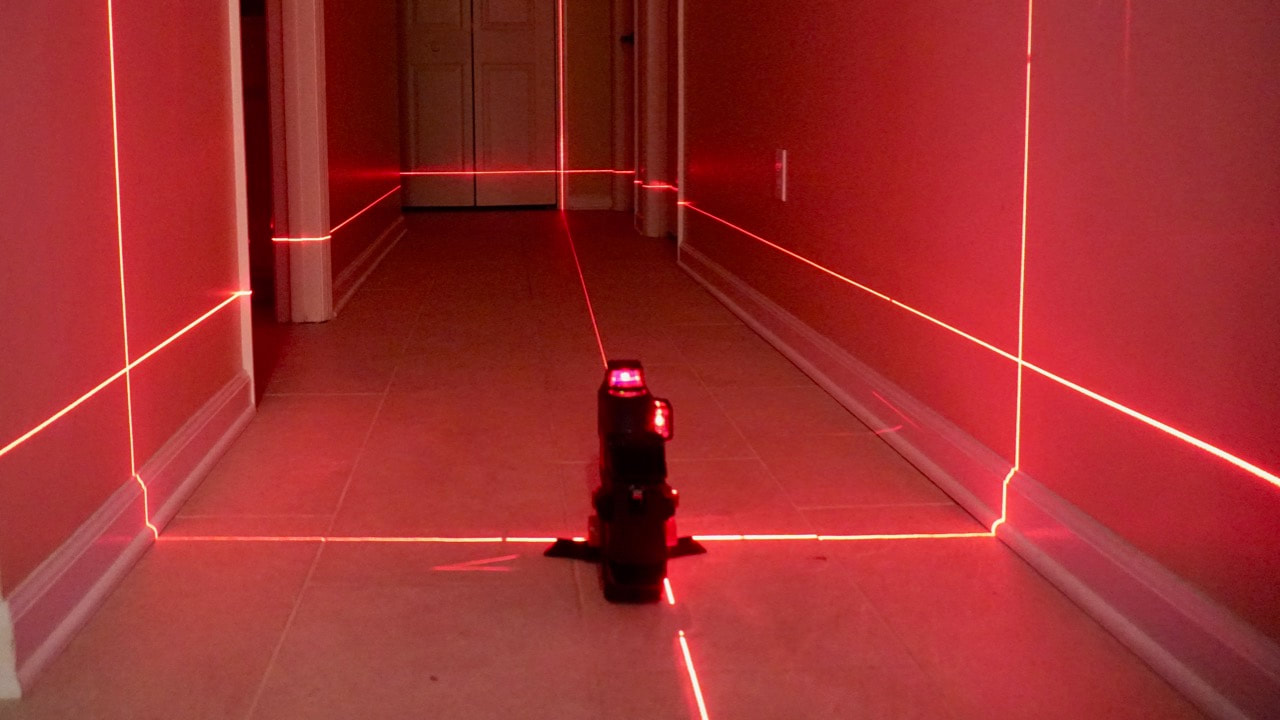 The Bosch laser level all lit up in a small hallway.