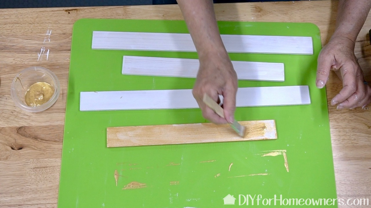Painting the frame pieces over a Surebonder silicone mat for hot glue.